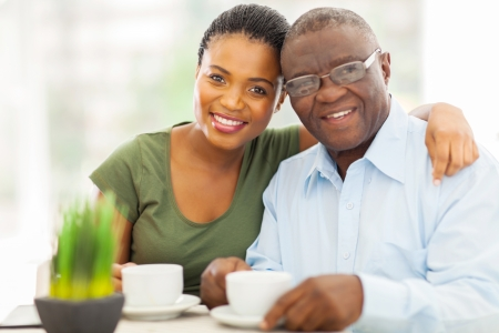 calm woman: beautiful young adult african girl and father having coffee at home