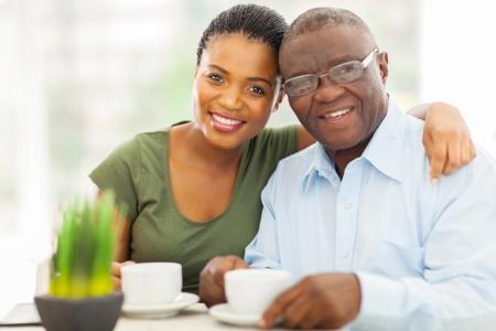 abuelitos: hermosa joven adulta ni�a africana y el padre que tiene el caf� en casa Foto de archivo