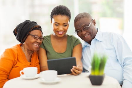 senior african: pretty young adult african girl with senior parents using tablet computer