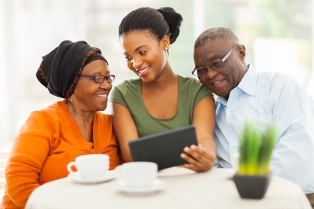 grandparents: cheerful african family at home using tablet pc Stock Photo
