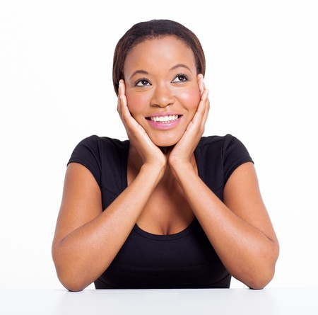 young woman sitting: cheerful african american woman looking up isolated on white