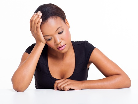 sad person: sad african american woman sitting at a desk on white background