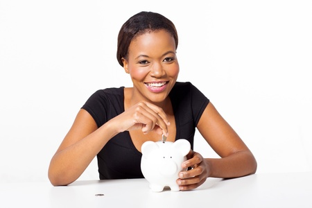 pretty africa woman putting coin in piggy bank isolated on white photo
