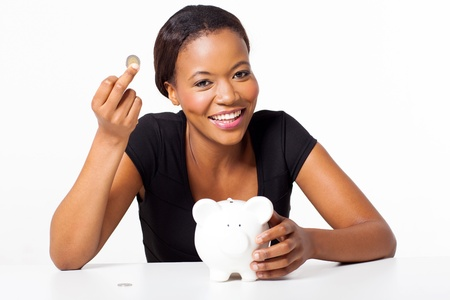 happy young black woman holding a coin and piggybank photo