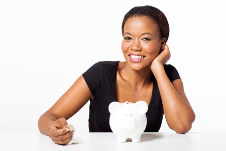 woman holding money: portrait of beautiful african woman holding coin with piggybank on white background Stock Photo
