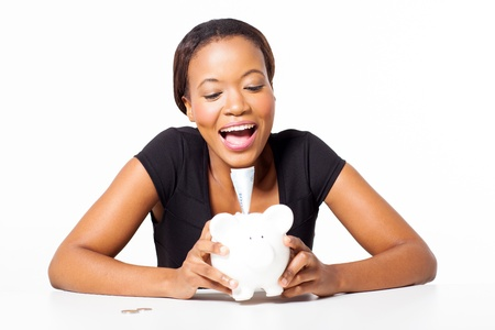 cheerful young african woman sitting with piggybank on white background photo