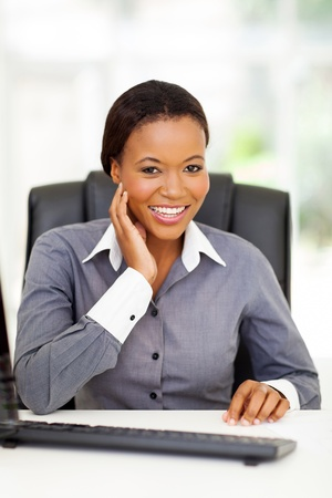 beautiful african american businesswoman sitting in office photo