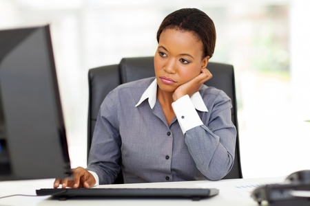thoughtful african american businesswoman looking at computer screen in office Stock Photo - 22138406