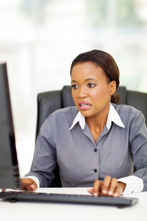 surprised african office worker working on computer Stock Photo - 22138598