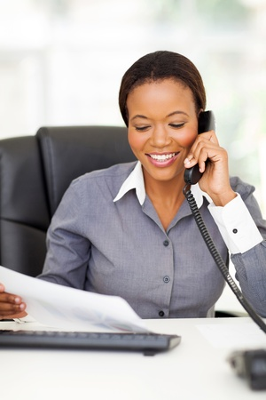 business attire: happy african american office worker talking on landline phone Stock Photo