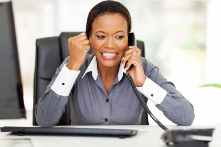 employee: excited african american businesswoman hearing good news on the phone Stock Photo