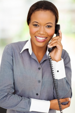 happy african businesswoman using landline phone photo