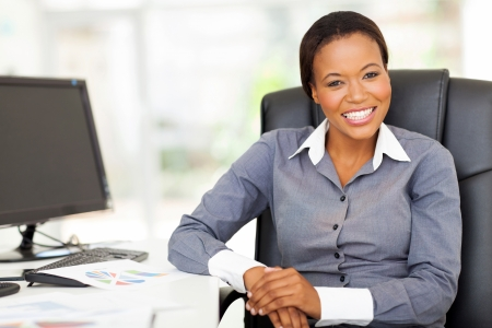 african american businesswoman: smiling african businesswoman sitting in office looking at the camera Stock Photo
