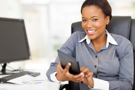 ethnic attire: attractive african businesswoman using tablet computer in office