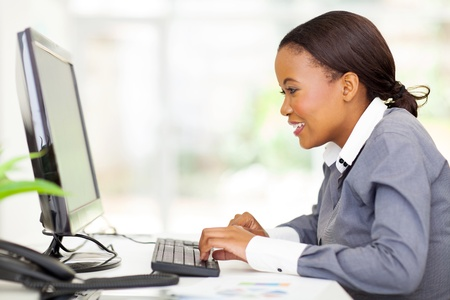 pretty african businesswoman looking at computer screen Stock Photo - 22138678