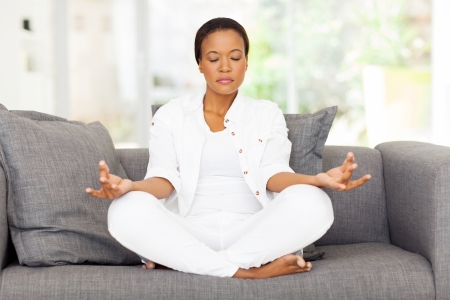 beautiful young african woman meditating at home photo