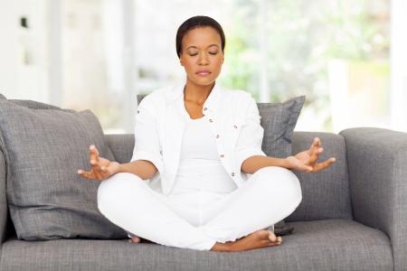 mujer meditando: joven y bella mujer meditando africano en su casa