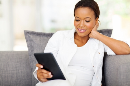 pretty african woman using tablet computer at home photo