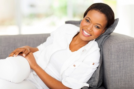 afro american: happy african woman lying on a couch