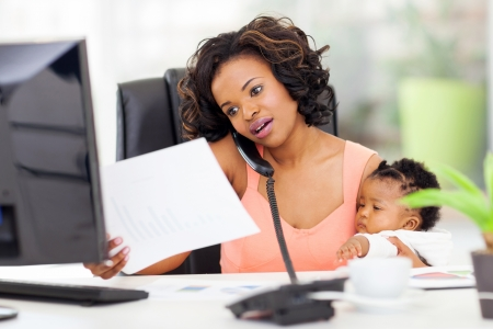 african american woman with baby girl working from home photo