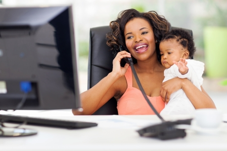 women working: successful african businesswoman talking on landline phone while holding her little baby girl