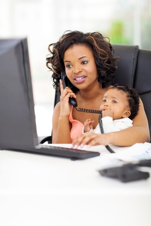 successful young african american businesswoman with baby at office photo