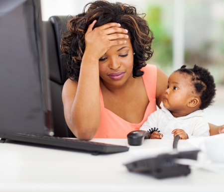 modern parents: frustrated african american businesswoman with her little baby in office