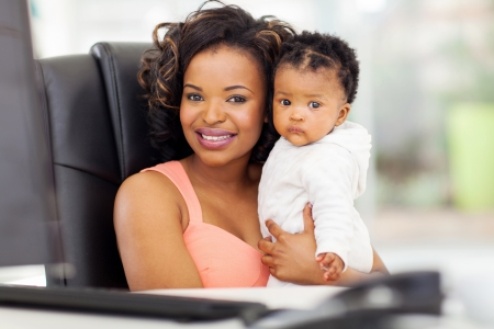 beautiful african american businesswoman holding her baby in office photo