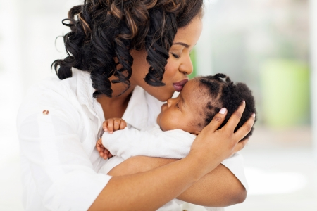toddler girl: loving african american woman kissing her baby girl Stock Photo