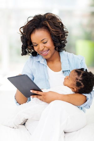 cheerful young african mother holding her baby while using tablet computer at home photo