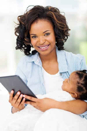 pretty young african mother holding tablet computer with baby at home photo