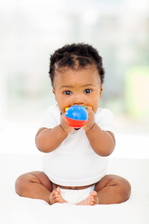 cute african baby girl biting her toy photo