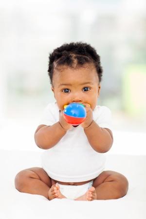 bebekler: sevimli zenci kız bebek oyuncak ısırma Stok Fotoğraf