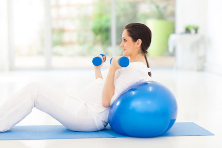 pretty pregnant woman exercising with dumbbells at home photo