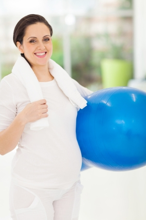 gorgeous caucasian pregnant woman holding fitness ball at\ home