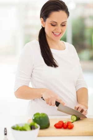 cute young pregnant woman cooking in kitchen photo