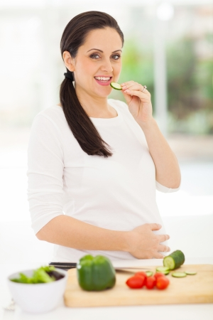 happy pregnant woman eating slice of cucumber photo