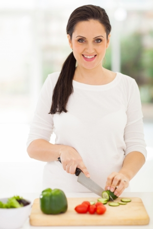 portrait of pregnant woman cutting vegetables photo