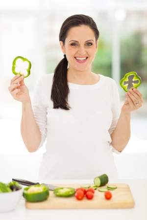 cheerful pregnant woman showing slices of green pepper photo