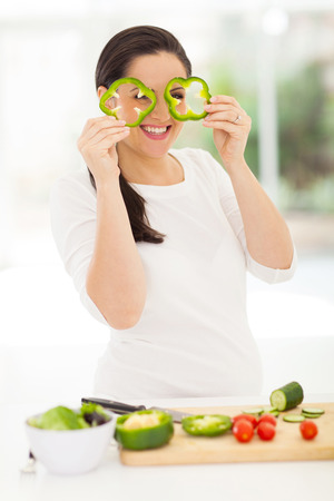 playful pregnant woman holding slices of green pepper photo