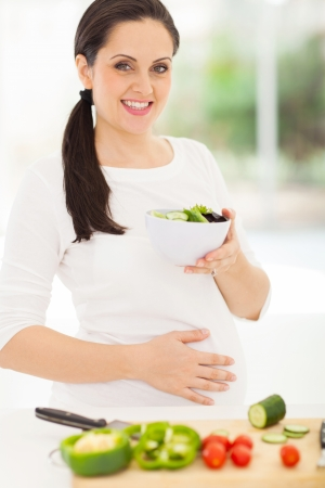 pretty pregnant woman holding bowl of green salad in kitchen photo