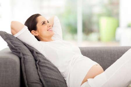 happy pregnant woman lying on couch daydreaming photo