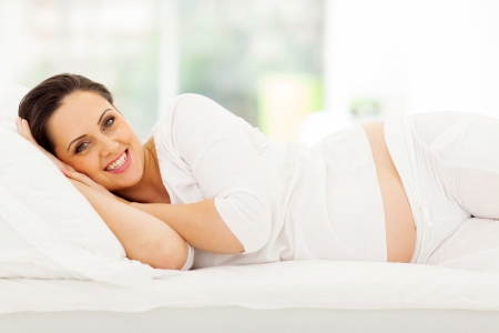 happy pregnant woman lying on bed at home photo