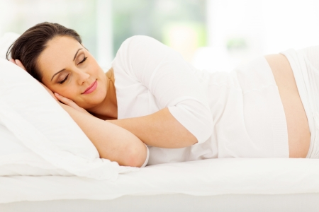 beautiful young pregnant woman sleeping peacefully in bed photo