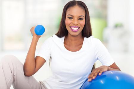 cabello negro: feliz mujer afroamericana haciendo ejercicio de gimnasio en casa Foto de archivo