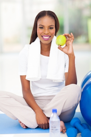 healthy african american woman holding apple after working out photo