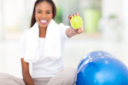 healthy african woman holding a green apple photo