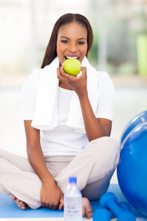 young african american woman eating apple after exercise photo