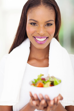 woman towel: cheerful young african woman with bowl of fresh salad