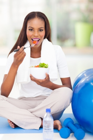 pretty afro american woman eating salad on exercise mat photo